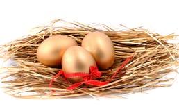 Trois oeufs d'or dans le nid d'isolement sur le fond blanc Photos stock