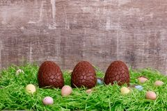 Trois oeufs de chocolat et oeufs de caille sur une herbe verte devant un fond en bois Carte de voeux de Pâques Photographie stock