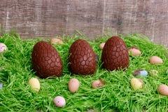Trois oeufs de chocolat et oeufs de caille sur une herbe verte devant un fond en bois Carte de voeux de Pâques Images stock