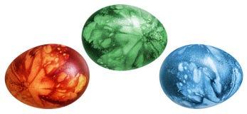 Trois oeufs de pâques colorés peints à la main et décorés des empreintes de feuilles de mauvaise herbe d'isolement sur le fond bl Photographie stock libre de droits
