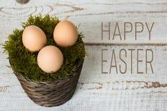 Trois oeufs de pâques dans un panier de mousse, concept heureux de Pâques, rétro fond de Pâques Images stock