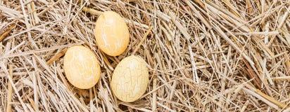 Trois oeufs de pâques jaunes en paille Photos libres de droits