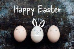Trois oeufs de pâques mignons avec des visages, fond heureux de lapin de Pâques Image libre de droits