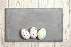 Trois oeufs de pâques peints d'un plat concret sur un fond clair image libre de droits