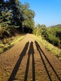 Trois ombres sur la route Photo stock