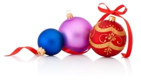 Trois ont coloré des babioles de Noël avec l'arc de ruban d'isolement sur le blanc Image stock
