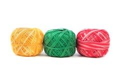 Trois ont coloré des fils de couture dans une rangée sur un fond blanc Fils bleus, verts et jaunes Photo stock