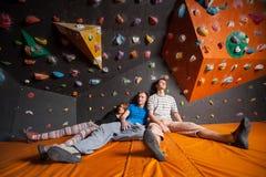 Trois ont fatigué des grimpeurs sur le tapis près du mur de roche à l'intérieur Photo stock