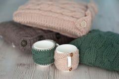 Trois ont tricoté des oreillers et deux tasses sur le fond de conseil en bois Image libre de droits