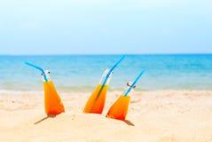 Trois orange Juice Bottles Sea Background Summer Images stock