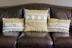 Trois oreillers de toile de jute avec la dentelle blanche sur un divan en cuir images stock