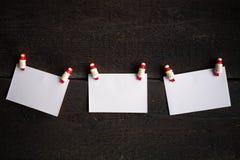 Trois pages de papier blanches attachées à une corde cheville le concept de Noël Photos libres de droits