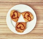 Trois pains frits dans l'oeuf avec des coeurs de ketchup, valentine Photographie stock