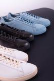 Trois paires d'espadrilles sur le fond noir Chaussure noire, blanche et bleue Image stock