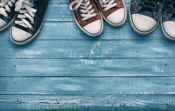 Trois paires d'espadrilles sur un fond bleu en bois Photos stock