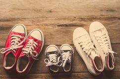 Trois paires de chaussures s'étendent sur le plancher en bois de la famille, photos libres de droits