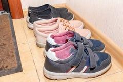 Trois paires de chaussures de sport - bottes, espadrilles, chaussures de course dans le couloir photographie stock libre de droits