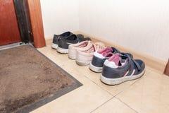 Trois paires de chaussures de sport - bottes, espadrilles, chaussures de course dans le couloir photographie stock