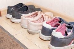 Trois paires de chaussures de sport - bottes, espadrilles, chaussures de course dans le couloir photos stock