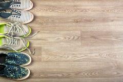 Trois paires de diverses chaussures de course se sont étendues sur un fond en bois de plancher Photographie stock libre de droits