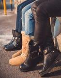 Trois paires de jambes de filles avec des bottes sur elles Images stock