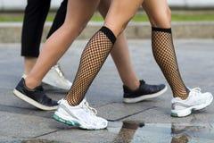Trois paires de jambes minces de jeunes filles d'ajustement dans le sport différent chausse la marche rapidement le long de la ro photos stock