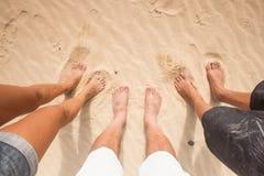 Trois paires de pieds dans le sable Photo stock