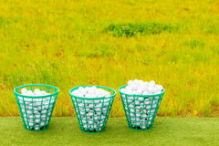 Trois paniers ont rempli de boules de golf sur l'herbe Photos stock