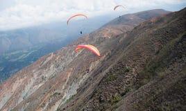 Trois parapentistes oranges énormes volent le long de la pente de la montagne énorme au-dessus de la vallée verte Photos stock