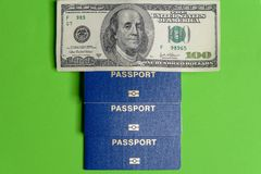 Trois passeports biométriques bleus avec cent dénominations du dollar photographie stock