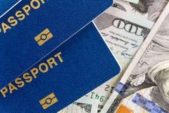 Trois passeports internationaux biometrical au-dessus de fond d'argent Documents de voyage bleus se trouvant sur les USA cent bil photographie stock