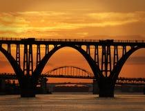 Trois passerelles sur le fleuve au coucher du soleil Photographie stock