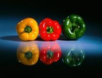 Trois pepers colorés sur un tableau 2 Photos stock