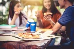 Trois personnes asiatiques ont plaisir à manger de la pizza à l'extérieur après soutien scolaire photographie stock libre de droits