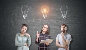 Trois personnes avec des croquis d'ampoule au-dessus de leurs têtes Image stock