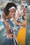 Trois personnes convenables établissant sur des vélos d'exercice photos libres de droits