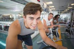 Trois personnes convenables établissant sur des vélos d'exercice photo libre de droits