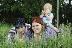 Trois personnes dans l'herbe Photo stock