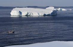 Trois personnes en bateau et icebergs Photos stock