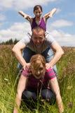 Trois personnes font un saut de saute-mouton Photographie stock