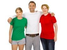Trois personnes utilisant les chemises vides blanches et rouges vertes Photos libres de droits