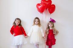 Trois petites belles filles dans des mains rouges de prise image libre de droits