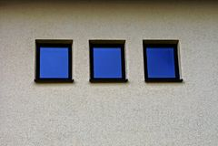 Trois petites fenêtres carrées sur le mur gris du bâtiment Images libres de droits