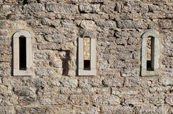 Trois petites fenêtres d'un bâtiment antique Image libre de droits