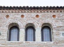 Trois petites fenêtres de voûte sur un mur de briques Photo libre de droits