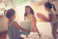 Trois petites filles ayant l'amusement sur le lit Photos stock