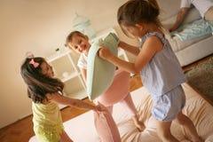 Trois petites filles ayant l'amusement sur le lit Images stock