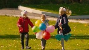 Trois petites filles ayant l'amusement sur le pré vert banque de vidéos