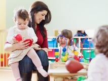Trois petites filles et professeur féminin Image stock