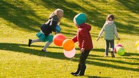 Trois petites filles prenant les ballons de l'herbe verte et jaune banque de vidéos